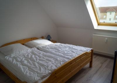 Schlafzimmer mit Doppelbett und Dachfenster